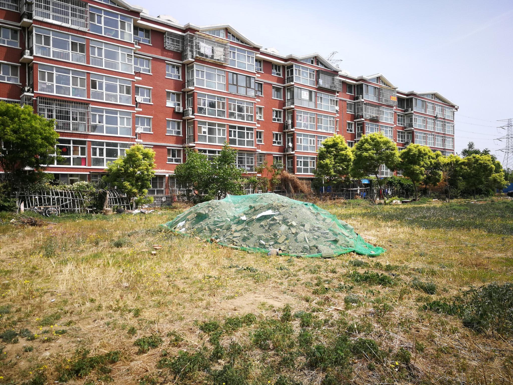 明明没人装修,小区绿地却常现大量建筑垃圾,实在诡异!